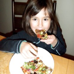 Photograph of Ella eating cauliflower crust pizza with her hands.